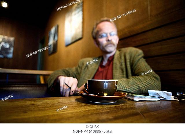 Mature man sitting in a cafe and thinking