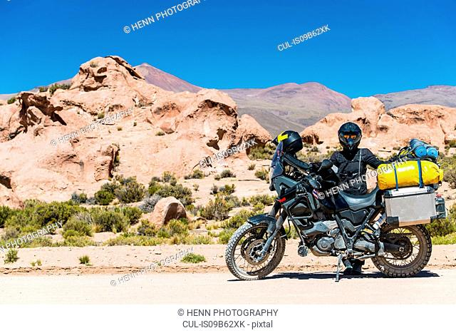Woman standing next to touring motorbike in desert, Uyuni, Oruro, Bolivia, South America