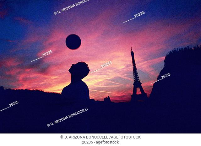 young man heads a soccer ball in front of the Eiffel Tower at sunset, Paris, France