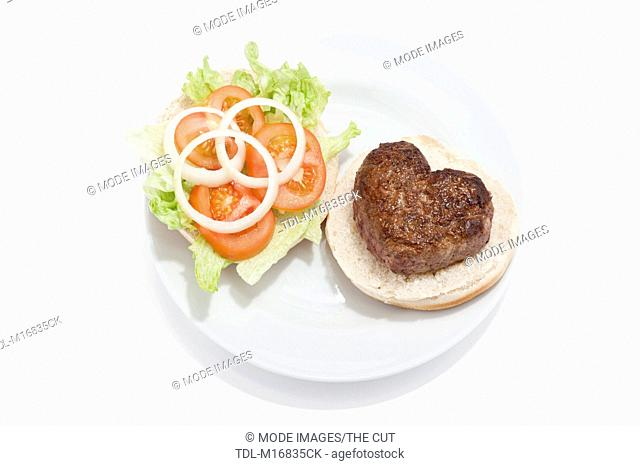 A heart shaped beef burger on a bun, with a side salad