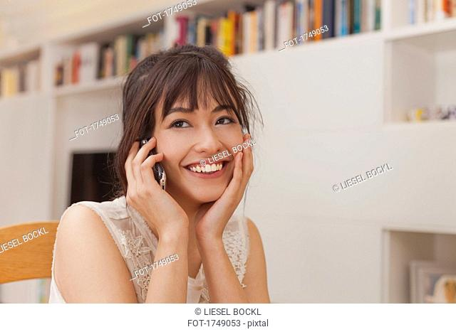 Smiling young woman talking on mobile phone at home