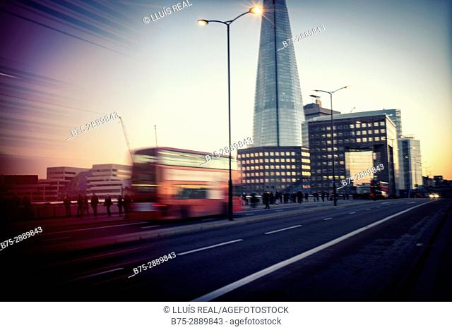 Bus in motion on London Bridge at dusk, The Shard building in background. London, England, UK