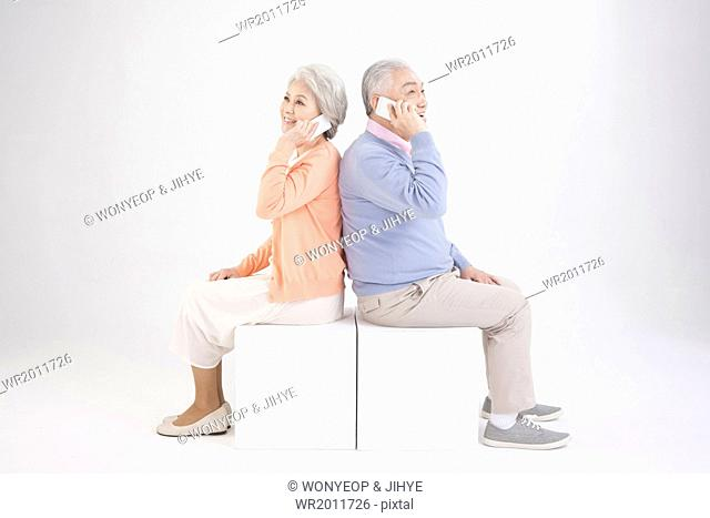 an old couple sitting back to back