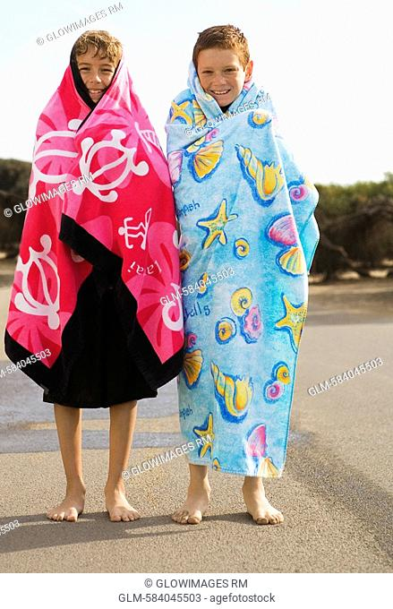 Two boys wrapped in beach towels