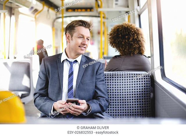 Formal businessman sitting on the train. He is holding a smartphone and looking out the window