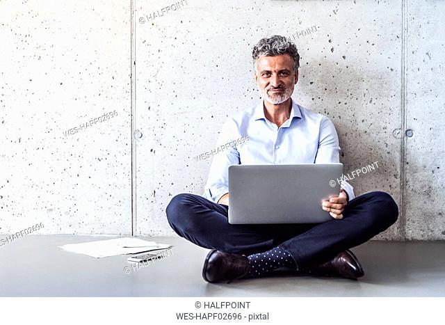 Portrait of confident mature businessman sitting on the floor using laptop
