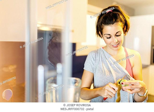 Young woman in kitchen peeling a kiwi