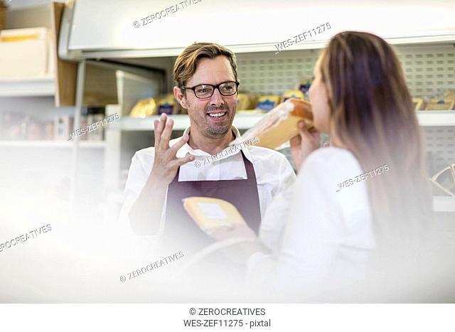 Portrait of grocer serving customer in a farm shop