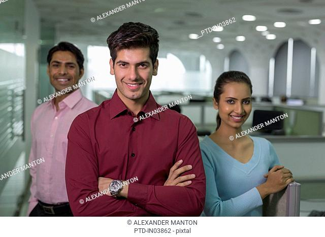 India, Smiling businessman in front of colleagues in office