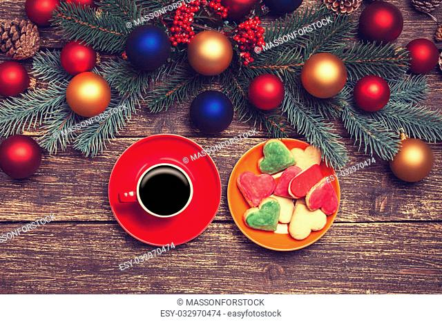 Hot coffee on a table near pine branches with chritmas balls on wooden table