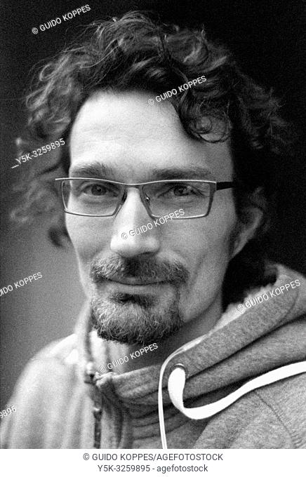 Tilburg, Netherlands. Black & White portrait of an adult, caucasian male wearing glasses and walking the streets down town. Shot on Analog Film