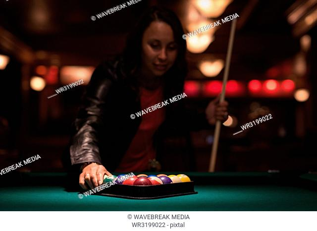 Woman arranging snooker balls in triangle rack