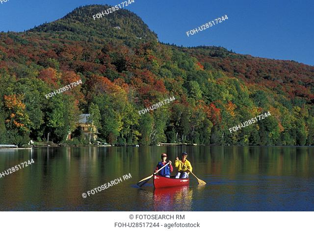 canoeing, Vermont, VT, Mother and daughter paddle a red canoe on Long Pond in Westmore in the fall surrounded by colorful foliage
