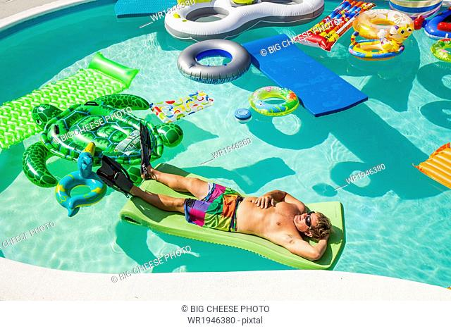 Man wearing flippers floats in a pool full of inflatable toys