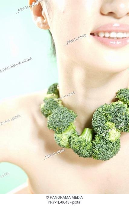 Close-up of woman with broccoli on neck