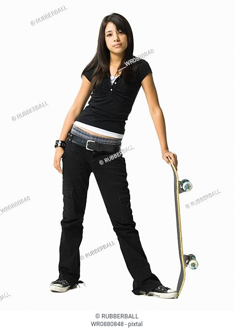 Teenage girl standing and holding a skateboard