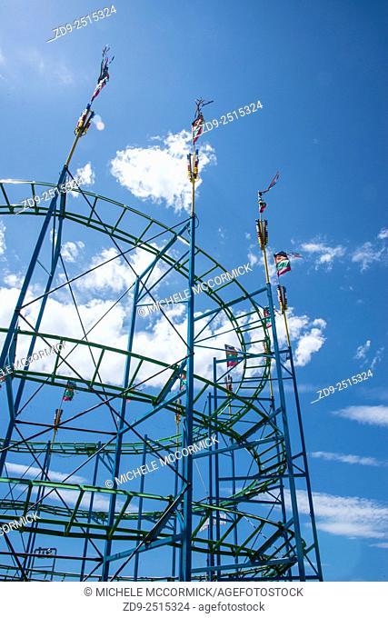 A carnival roller coaster against a blue sky