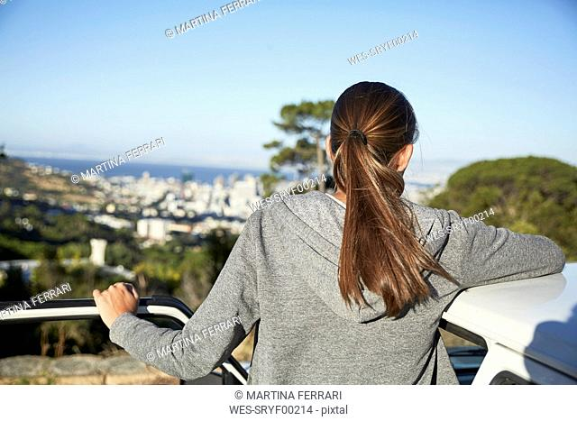 Back view of young woman leaning on car roof at sunlight