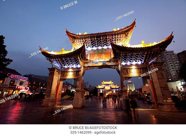 Night view of memorial arches of the Golden Horse and Jade Rooster in Jinmabiji Square, Kunming, China