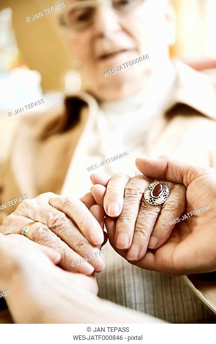 Adult daughter holding hands of her mother with Alzheimer's disease, close-up