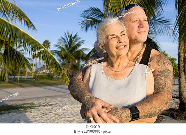 Mother and tattooed son hugging at the beach