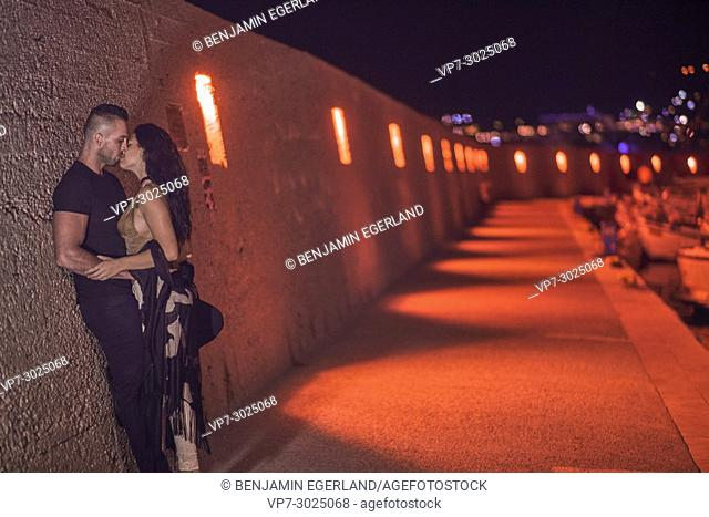 couple kissing in city lights at night. Greek ethnicity
