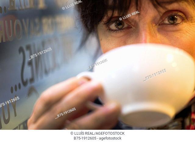 mature woman drinking coffee in a Tea Shop in Soho, London, England, UK