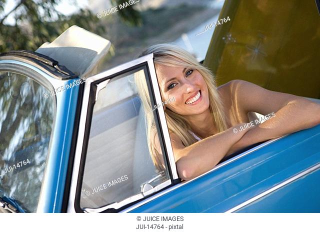 Woman in convertible car, smiling, portrait
