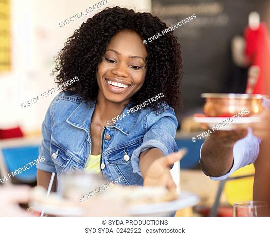 happy woman with friends eating at restaurant