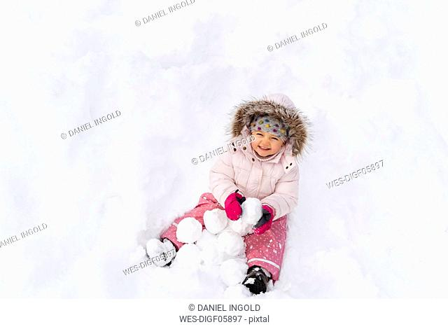 Cute little girl playing with snow in winter
