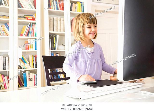 Smiling little girl spending time at computer