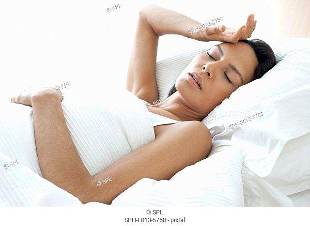 MODEL RELEASED. Young woman in bed with her hand on her forehead