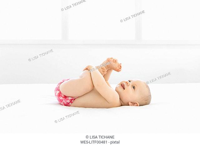 Happy baby playing around girl on white bed