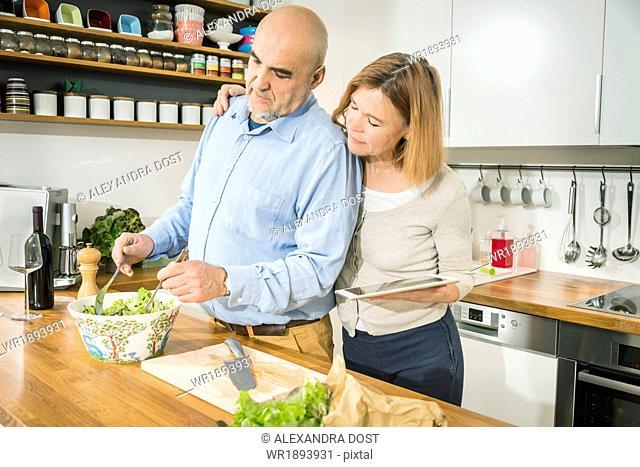 Senior couple preparing salad