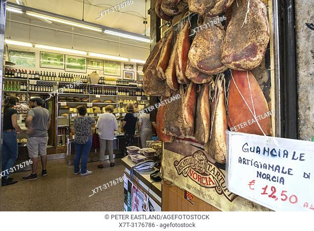 Hams hanging in the doorway and a sign advertising Guanciali, pork cheek, in a traditional delicatessen in the Trastevere district of Rome, central Italy