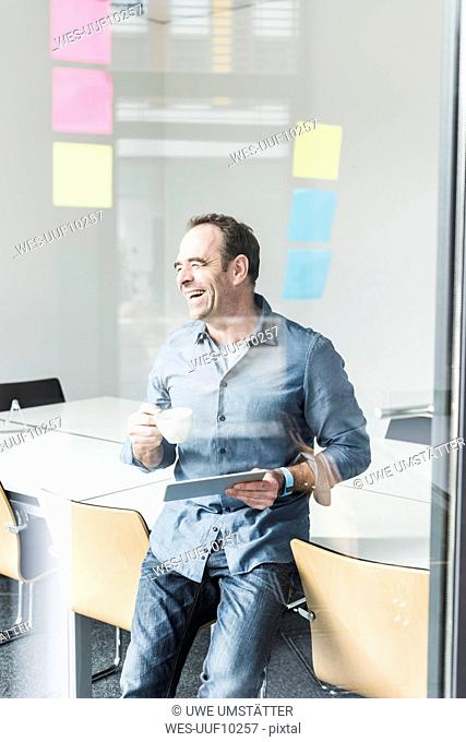 Laughing businessman with tablet looking sideways in office