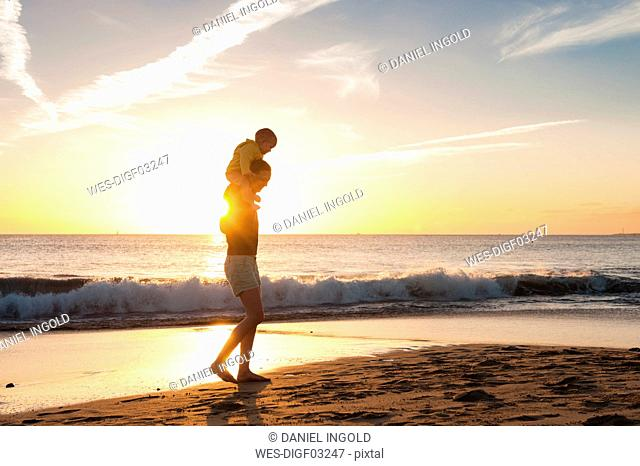 Mother walking with little daughter on the beach at sunset