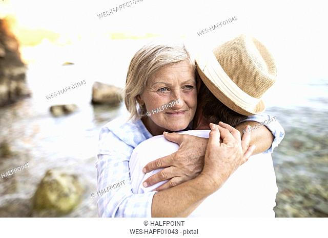 Portrait of content woman hugging her husband in front of the sea