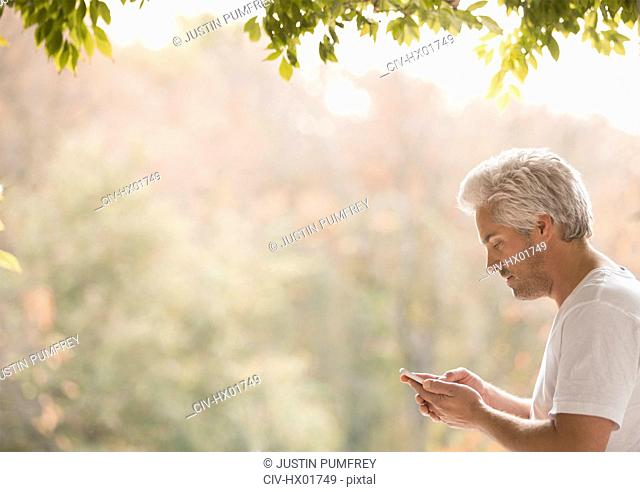 Man texting with cell phone on patio