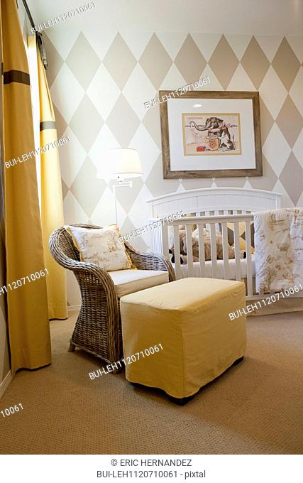 Baby's crib with floor lamp and picture frame in the house; San Marcos; California; USA