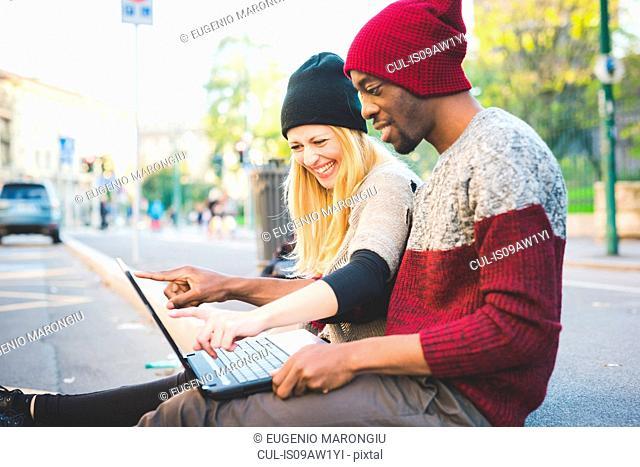 Couple using laptop on pavement