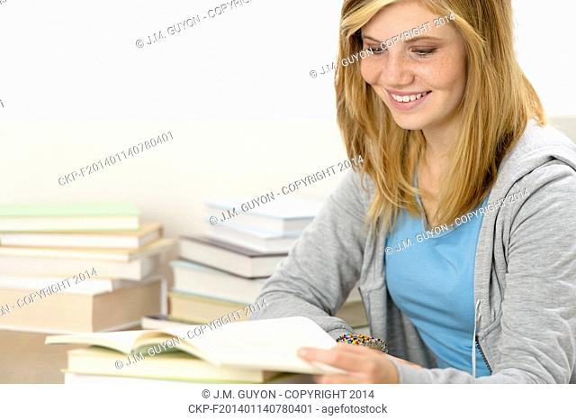 Smiling student girl reading book looking down sitting behind desk