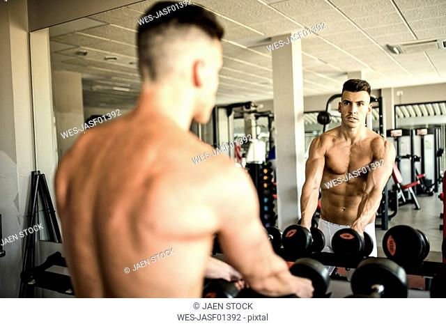 Man lifting weights in front of mirror