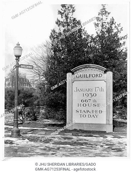 """Photograph of the corner of Greenway street in Guilford neighborhood in Baltimore, with a large stone sign reading """"""""January 17 1930 667th House Started Today"""