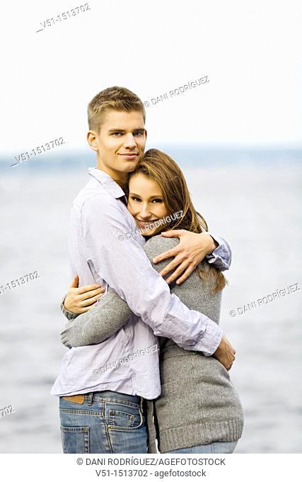 Portrait of a young couple embraced by the sea