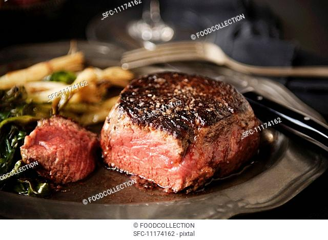 Angus Prime Aged Filet; Sliced on a Plated with Wilted Greens