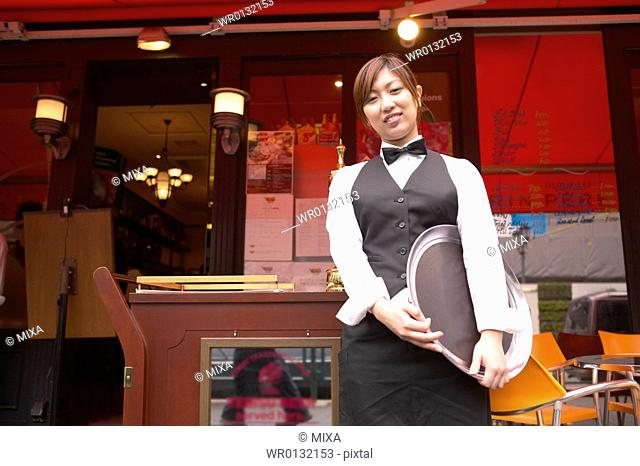 Waitress standing in front of coffee shop