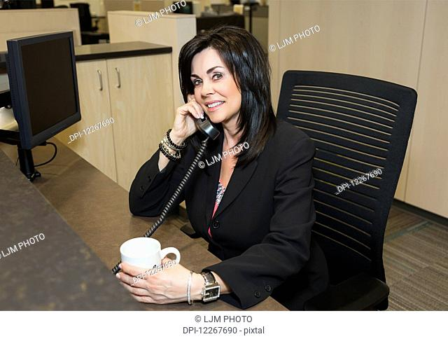 Professional businesswoman talking on the phone at her desk; Edmonton, Alberta, Canada