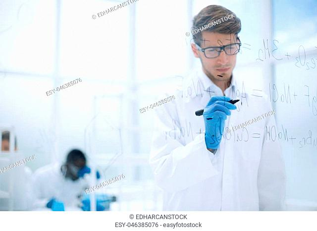 young scientist making notes on the glass Board at the time of the experiment.photo with copy space