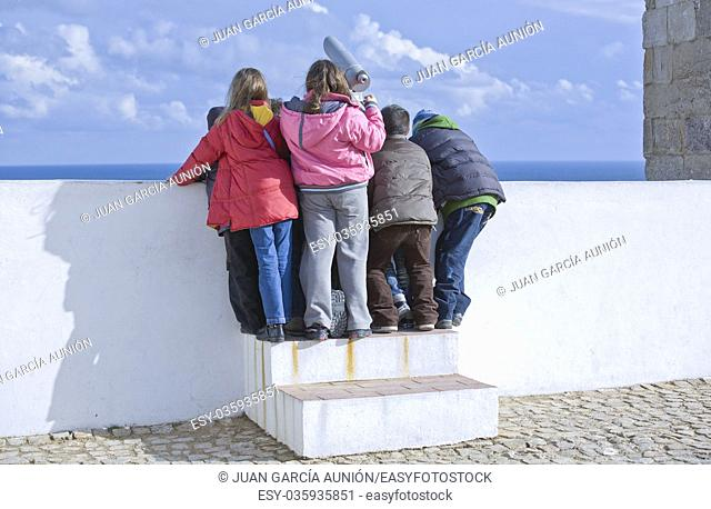 Unidentified children trying to use the telescope on the observation deck of the lighthouse wall in Sagres, Portugal
